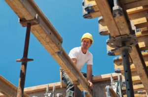 construction worker placing slab formwork beams in construction site